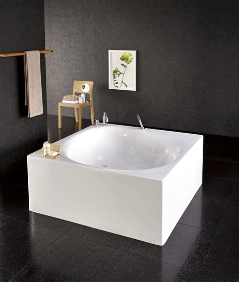 square bathtub with shower bathroom bathroom with outside view and small oval