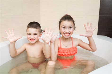 cute happy little brother and sister taking bath stock