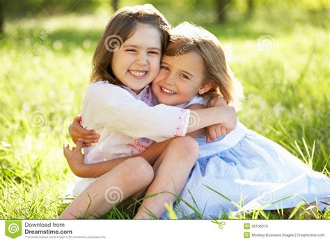 how to cuddle with a girl on the couch two young girls hugging in summer field stock photo