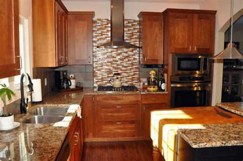 giallo fiorito granite with oak cabinets primary cabinetry in cherry island in black painted maple