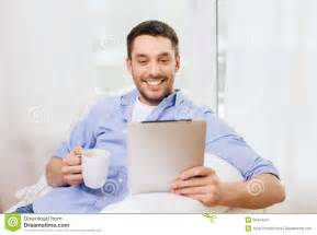 smiling with tablet pc and cup at home stock image