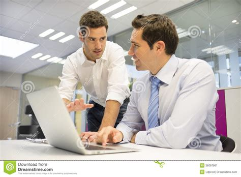 two handsome businessmen working together on a laptop in