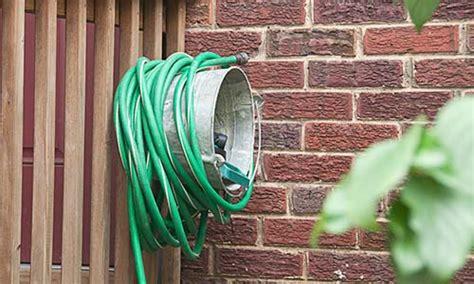 reader metal pail turned garden hose organizer