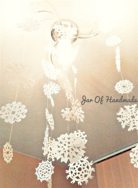 How To Make Hanging Paper Snowflakes - jar of handmade diy paper snowflakes hanging from the