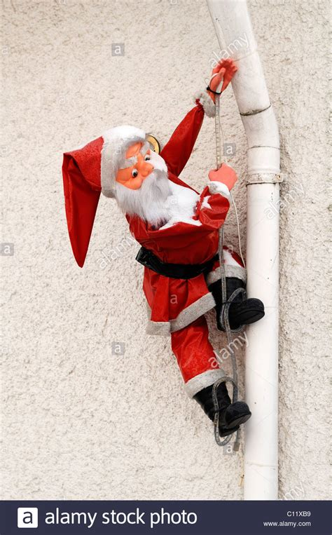 santa claus figure climbing gutter stock photo royalty