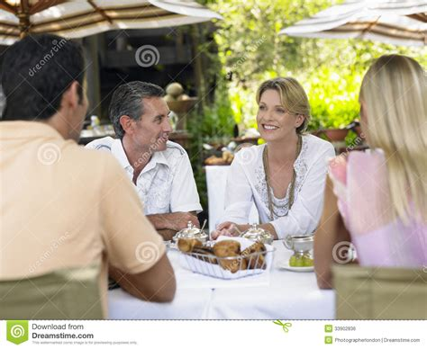 Two Couples Two Couples At Outdoor Table Chatting Stock Photo Image