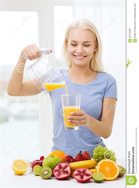 Detox Person by Smiling Pouring Fruit Juice To Glass At Home Stock