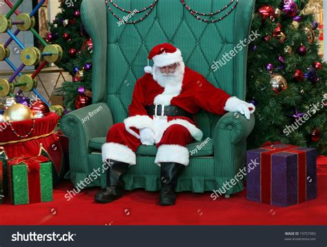 sleeping santa claus in big green chair surrounded by