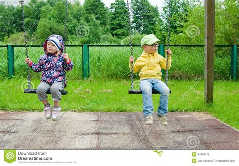 swinging on a swing young children swinging on a swing stock photo image