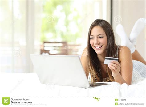 online bed shopping shopper shopping online with credit card and laptop stock