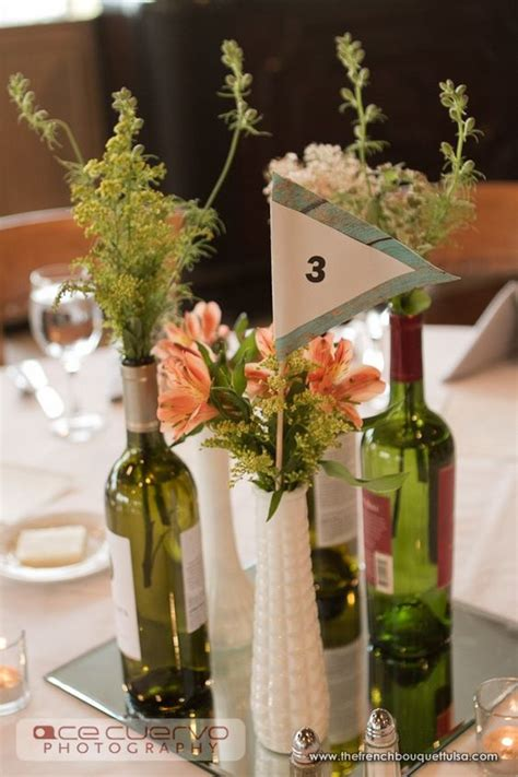 wine centerpieces for weddings flowers and greenery in milk glass vases and wine bottle for wedding reception
