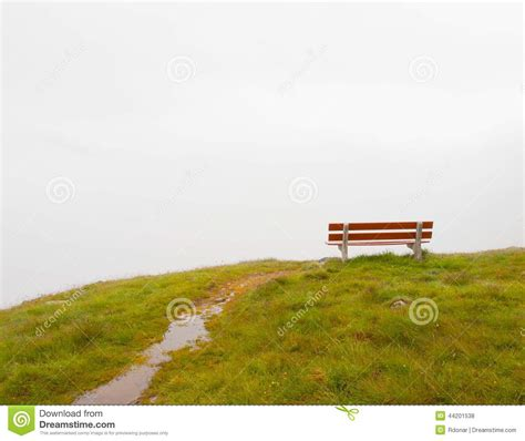 oppisite of red white grey clouds in opposite of red wooden bench on