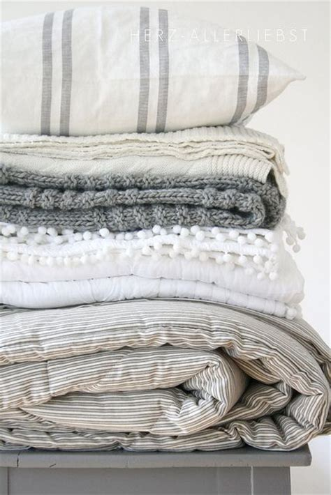 gray linen bedding a pile of white and grey squishy blankets throws and