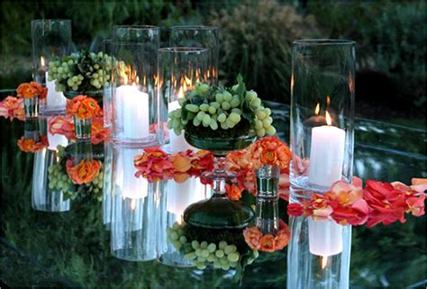 bright orange and coral petals strewn on mirrored