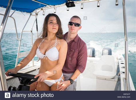 women on boats young woman in bikini and young man riding a boat at sea