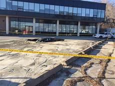 parking lot sinkhole swallows jaguar driver escapes