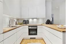 biała nowoczesna kuchnia z drewnianym blatem kuchnia