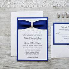 ivory lace wedding invitation with royal navy blue ribbon and silver rhinestone buckle