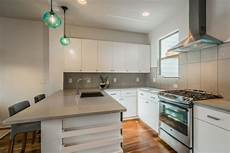 modern kitchen with light gray large tile backsplash and matching gray countertop and blue