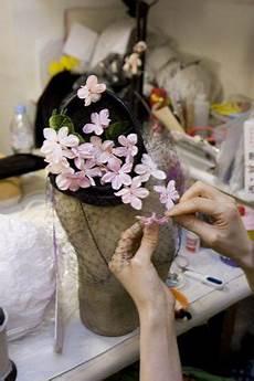 milliner mitsumi kinoshita applying flowers to a veiled hat at stephen jones millinery covent