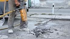 Bohren In Beton - worker drilling concrete with compressor stock footage