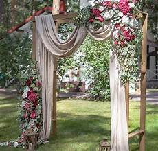 beautiful wedding ceremony backdrop arbor with draping flowers and lantern accents wedding