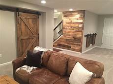 barn doors and pallet wall in the basement walls are agreeable gray by sherwin williams