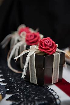 picture of black boxes with white ribbons and red roses on