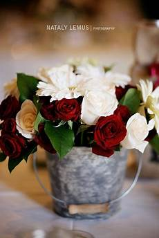 red and white flowers and roses wedding centerpiece in a