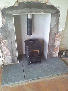 burning stove in a fireplace connected to a chimney liner fitting burning stove in a