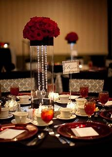 red rose centerpiece with bling hanging in the glass