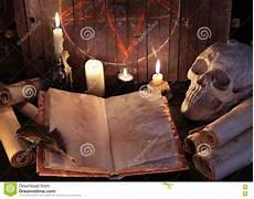 candele esoteriche open witch book with paper scrolls and evil candles