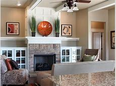 Built in white cabinets flank a brick fireplace with