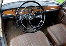 deze bmw 2000 sedan in eigentijds beige met een bruin