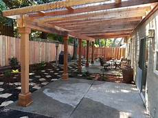 a water efficient back yard with a redwood pergola that has clear corrugated plastic for a roof