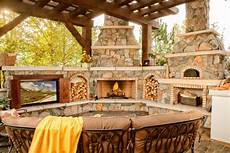 outdoor living space boasts tv fireplace and pizza oven