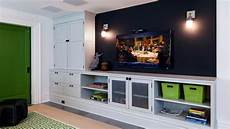 basement with tv wall painted in a dark color could be chalkboard paint and sconces hung on