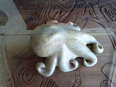 soapstone carving this is a craved soap octopus on a carved teak