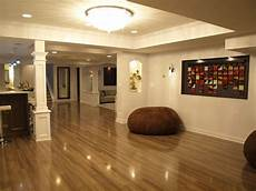 appealing basement remodeling with sleek brown laminate flooring and bar and white