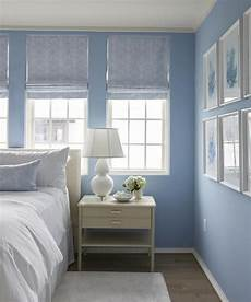 white and blue cottage bedroom boasts walls painted cornflower blue fitted with windows dressed