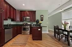 light green paint colors in kitchen with dark mahogany cabinets with black countertops wit