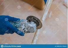 Worker In Gloves Uses Grinder For Cutting Tiles Porcelain