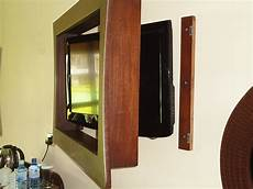 Lcd Tv Mounted On Wall Surrounded By A Wooden Hinged Frame