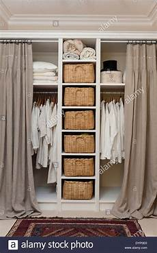 White Shirts And Linens Hanging On Rails In Open Storage