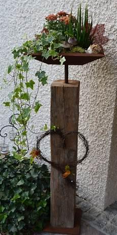 altholzbalken mit edelrost schale herbstlich dekoriert