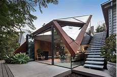 angular corten roof folds down over leaf house extension