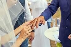 in white putting wedding ring grooms finger