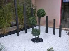 idee deco jardin gravier 36208 parterre avec cailloux massif contemporain taupi 232 re piquets d ardoise galets noirs et