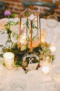 your reception tables with glowing votive candles gold caged hurricane vases and moss