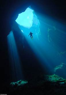spectacular images of divers exploring water filled cavern